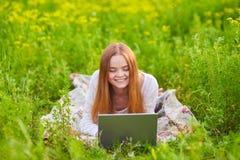 Ragazza sorridente con il computer portatile su erba Fotografia Stock
