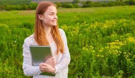 Ragazza sorridente con il computer portatile su erba Immagini Stock Libere da Diritti