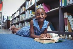 Ragazza sorridente con il libro che si trova dallo scaffale in biblioteca Fotografia Stock