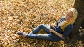 Ragazza sorridente con il pc della compressa sull'autunno Immagine Stock
