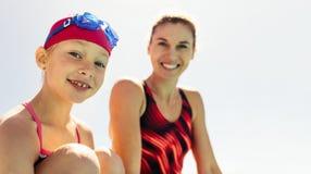 Ragazza sorridente con l'istruttore di nuoto immagini stock