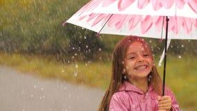 Ragazza sorridente con l'ombrello sotto pioggia archivi video