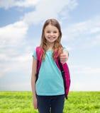 Ragazza sorridente con la borsa di scuola che mostra i pollici su Immagine Stock Libera da Diritti