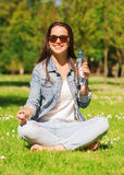 Ragazza sorridente con la bottiglia di acqua in parco Fotografia Stock Libera da Diritti