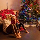 Ragazza sorridente con la mamma vicino all'albero di Natale a casa Immagini Stock Libere da Diritti