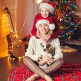 Ragazza sorridente con la mamma vicino all'albero di Natale a casa Fotografie Stock