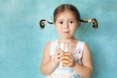 Ragazza sorridente con le trecce divertenti con vetro di succo Fotografia Stock