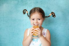 Ragazza sorridente con le trecce divertenti con vetro di succo Immagini Stock