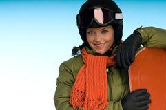 Ragazza sorridente con lo snowboard arancione Fotografie Stock