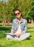 Ragazza sorridente con scrittura del taccuino nel parco Fotografia Stock Libera da Diritti
