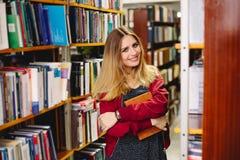 Ragazza sorridente con un libro in biblioteca universitaria Concetto di formazione Immagini Stock