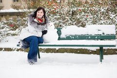 Ragazza sorridente con un piccolo pupazzo di neve Fotografie Stock Libere da Diritti