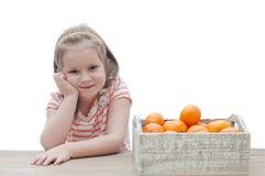 Ragazza sorridente con una scatola di mandarini sopra fondo bianco Fotografia Stock Libera da Diritti