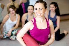 Ragazza sorridente degli Yogi con la stuoia di yoga immagine stock libera da diritti
