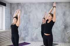 Ragazza sorridente degli Yogi nella classe in asana di yoga, esercitandosi, allungante fotografia stock libera da diritti