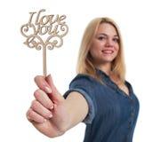 Ragazza sorridente dei capelli biondi che giudica un ` di legno del ` del segno ti amo disponibile Fotografia Stock Libera da Diritti