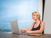 Ragazza sorridente dei pantaloni a vita bassa che chiacchiera nella rete sociale tramite computer portatile moderno Fotografia Stock Libera da Diritti