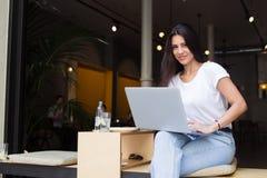 Ragazza sorridente dei pantaloni a vita bassa che esamina la macchina fotografica mentre lavorando al computer portatile in caffe Fotografia Stock