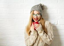Ragazza sorridente dei pantaloni a vita bassa in vestiti di inverno con la tazza immagine stock