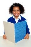 Ragazza sorridente del banco che impara assegnazione settimanale Fotografia Stock