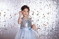 Ragazza sorridente del piccolo bambino in vestito d'argento sul fondo dei coriandoli fotografia stock libera da diritti