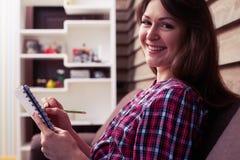 Ragazza sorridente deliziosa che esamina la macchina fotografica mentre tenendo a non Fotografia Stock