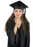Ragazza sorridente dell'allievo di graduazione che mostra shh Fotografia Stock