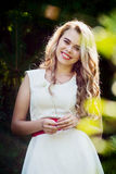 Ragazza sorridente della foto di estate in un vestito bianco Immagine Stock