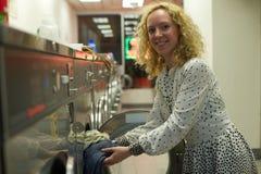 Ragazza sorridente della lavanderia automatica che inserisce i vestiti fotografia stock