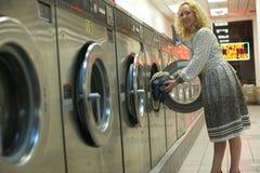Ragazza sorridente della lavanderia automatica che inserisce i vestiti immagine stock libera da diritti