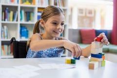 Ragazza sorridente della scuola che gioca con la particella elementare in biblioteca Fotografia Stock
