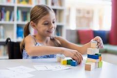 Ragazza sorridente della scuola che gioca con la particella elementare in biblioteca Immagini Stock Libere da Diritti