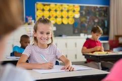 Ragazza sorridente della scuola che prende le note Fotografia Stock