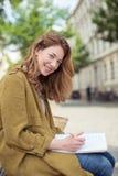 Ragazza sorridente della scuola sulla penna e sulle note di tenuta del banco Fotografie Stock Libere da Diritti