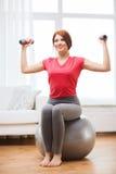 Ragazza sorridente della testarossa che si esercita con la palla di forma fisica Fotografie Stock