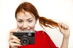 Ragazza sorridente della testarossa con vecchio camer Immagine Stock