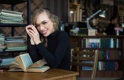 Ragazza sorridente dello studente alla biblioteca che studia con i libri Fotografie Stock