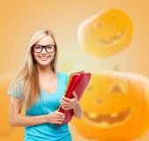 Ragazza sorridente dello studente con i libri e lo zaino Fotografie Stock