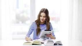 Ragazza sorridente dello studente con il pc ed i libri della compressa