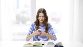 Ragazza sorridente dello studente con lo smartphone ed i libri archivi video
