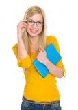 Ragazza sorridente dello studente in vetri con il libro Immagine Stock