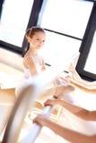 Ragazza sorridente di balletto che allunga la sua gamba facendo uso di Antivari Fotografia Stock Libera da Diritti