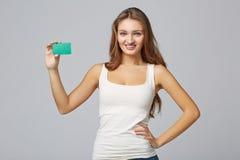 Ragazza sorridente felice in abbigliamento casuale, mostrante la carta di credito in banca Fotografia Stock