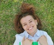 Ragazza sorridente felice con il libro che si trova sull'erba nel parco Immagine Stock Libera da Diritti