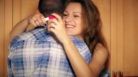 Ragazza sorridente felice con il test di gravidanza in mani che abbraccia con il suo ragazzo dell'uomo stock footage