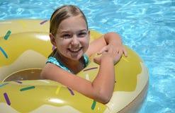 Ragazza sorridente in galleggiante dello stagno fotografia stock