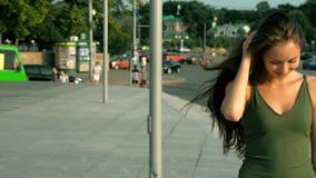 Ragazza sorridente graziosa che cammina giù la via che esamina la macchina fotografica video d archivio