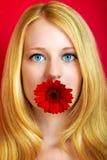 Ragazza sorridente graziosa con il fiore immagine stock