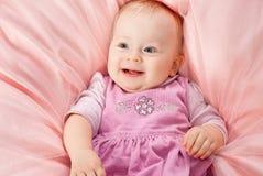 Ragazza sorridente infantile che si distende sul comforter Immagine Stock Libera da Diritti