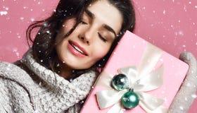 Ragazza sorridente in maglione e guanti che tengono il contenitore di regalo fotografia stock
